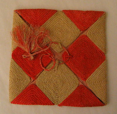 Folder made of string squares, natural and orange coloured in checker-board design