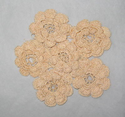 Crochet-work doily made from six flower-shaped roundels backed with a small piece of lace.