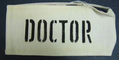 White cotton brassard with DOCTOR printed in black stencilled letters. Fastened with elastic.