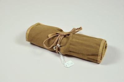 khaki surgical instrument roll, containing medical instruments