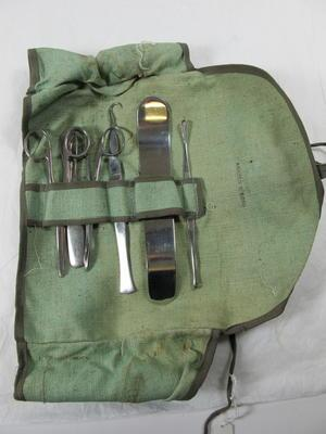light green surgical instrument roll, stamped Arnold & Sons, containing a mixed minor surgical kit
