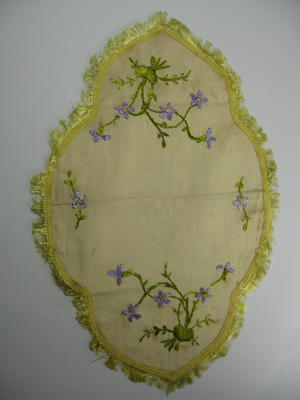 Yellow cloth with fringing on scalloped edges and decorated with embroidered purple flowers.