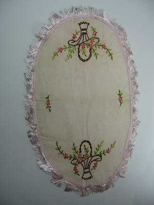 Pink cloth with fringed, scalloped edges and decorated with embroidered pink flowers in a basket.