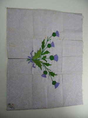 Rectangular piece of mauve silk decorated with embroidered thistles and with the words 'To Dorris' in one corner.