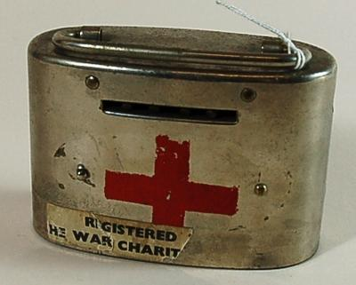 Metal collecting tin with handle and locking mechanism. Red cross emblem painted on front with torn label '...REGISTERED ... HE WAR CHARITY...'