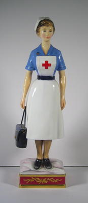 Royal Worcester figure of a British Red Cross VAD in indoor uniform carrying a First Aid bag