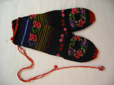 one pair of knitted socks in many colours, decorated with knitted flowers.
