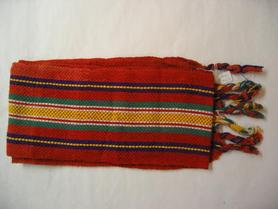 long woven braid, mainly in red but with purple, yellow, green and white, with four tassels at either end