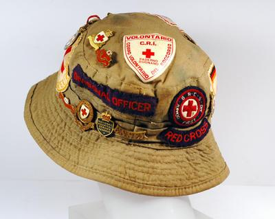 Khaki sunhat ('camp hat') with many Red Cross badges. Formerly belonged to Jean Davis, youth worker, of Maldon Centre.