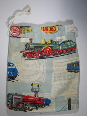 Comforts bag made from colourful cotton material depicting toys, with draw string top, and label 'BOYS'.