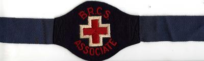 Textile brassard on textile strap with metal fastener. The brassard has the words 'B.R.C.S. Associate' around the red emblem edged in white.