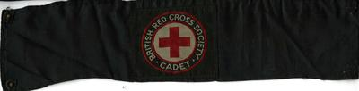 Brassard mounted on black material, fastened with two poppers. The brassard badge has the words 'British Red Cross Society Cadet' around the emblem.