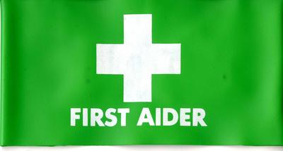 A PVC brassard in green with a white cross and the words 'First Aider'. There is a strip of elastic at the back.