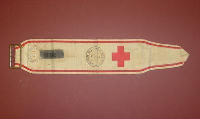 white armband with red trim and metal fastening