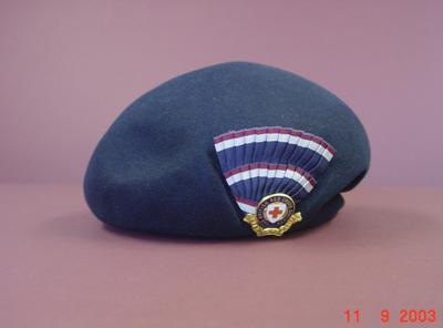 navy blue felt beret with cockade and hat badge to left of front