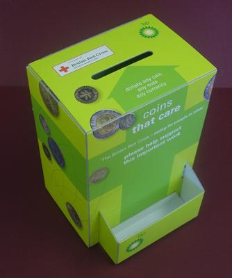Two tone green cardboard collecting box with front pouch and the words, 'Coins that Care' and images of coins. Front pouch holds BP logo