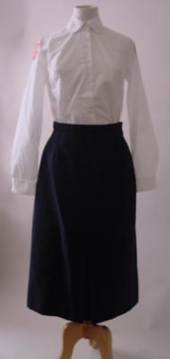 Ladies suit consisting of navy jacket, skirt and white blouse with insignia