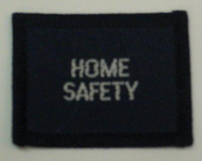 Navy blue cloth flash, to be worn on uniform by Red Cross Junior who holds a certificate in Home Safety. With the words 'Home Safety' in white.
