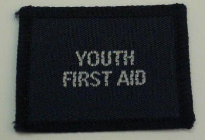 Navy blue cloth flash, to be worn on uniform by Red Cross Junior who holds a certificate in Youth First Aid. With the words 'Youth First Aid' in white.