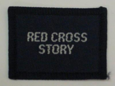 Navy blue cloth flash, to be worn on uniform by Red Cross Junior who holds a certificate in Red Cross Story. With the words 'Red Cross Story' in white.