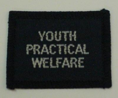 Navy blue cloth flash, to be worn on uniform by Red Cross Junior who holds a certificate in Youth Practical Welfare. With the words 'Youth Practical Welfare' in white.