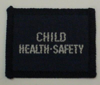 Navy blue cloth flash, to be worn on uniform by Red Cross Junior who holds a certificate in Child Health-Safety. With the words 'Child Health-Safety' in white.