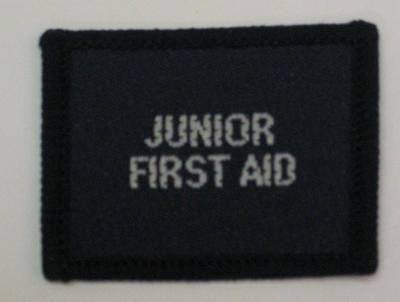 Navy blue cloth flash, to be worn on uniform by Red Cross Junior who holds a certificate in Junior First-Aid. With the words 'Junior First-Aid' in white.