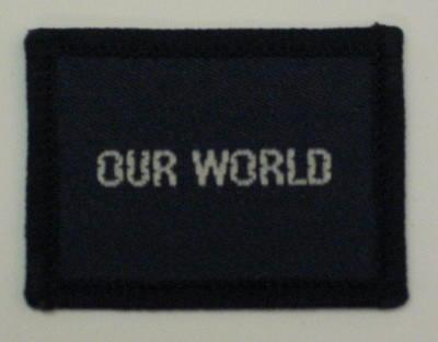 Navy blue cloth flash, to be worn on uniform by Red Cross Junior who holds a certificate in Our World. With the words 'Our World' in white.
