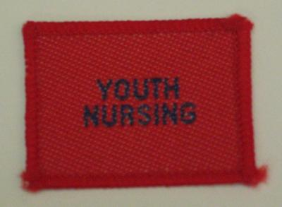 Red cloth flash, to be worn on uniform by Red Cross Youth who holds a certificate in Youth Nursing. With the words 'Youth Nursing' in white.