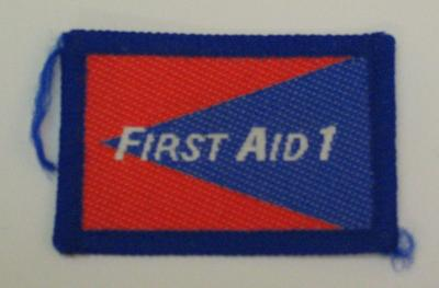 Red and blue cloth flash, to be worn on uniform by Red Cross Youth who holds a certificate in First Aid 1. With the words 'First Aid 1' in white.