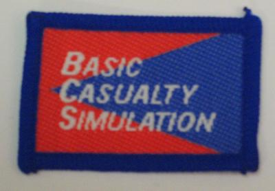 Red and blue cloth flash, to be worn on uniform by Red Cross Youth who holds a certificate in Basic Casualty Simulation. With the words 'Basic Casualty Simulation' in white.