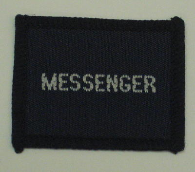 Navy blue cloth flash, to be worn on uniform by Red Cross Junior who holds a certificate in Messenger. With the words 'Messenger' in white.