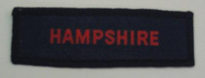 Navy blue County Branch cloth flash, with the word Hampshire in red.