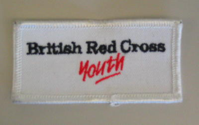 White cloth flash with the words 'British Red Cross Youth' in black and red.