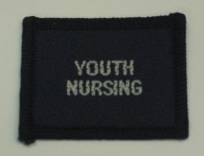 Navy blue cloth flash, to be worn on uniform by Red Cross Junior who holds a certificate in Youth Nursing. With the words 'Youth Nursing' in white.