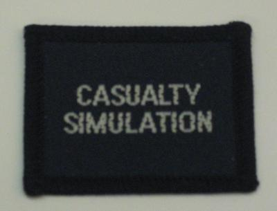 Navy blue cloth flash, to be worn on uniform by Red Cross Junior who holds a certificate in Casualty Simulation. With the words 'Casualty Simulation' in white.