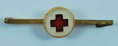 Small gilt-coloured tie pin with emblem inside white circle.