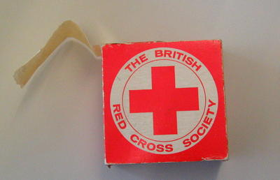 Cardboard box containing a roll of stickers. Each sticker is circular with the words 'The British Red Cross Society' around the emblem.