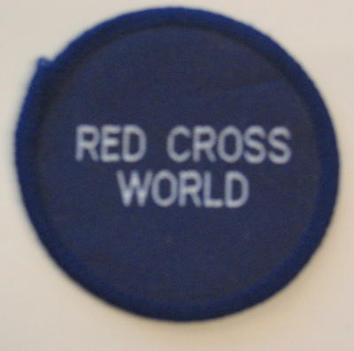Circular navy cloth badge: Red Cross World. To be sewn on to uniform.