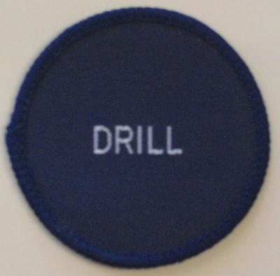 Circular navy cloth badge: Drill. To be sewn on to uniform.