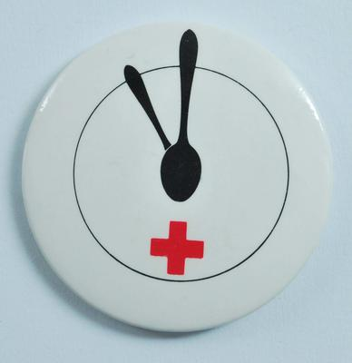 Circular plastic badge showing a spoon and an emblem on a clock face.