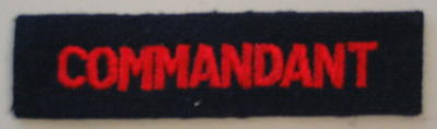 Cloth flash, red letters on navy blue: COMMANDANT