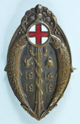 Oval-shaped brown badge, decorated with two fish, a bird, a bell and a tree.