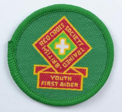 Green circular cloth badge: British Red Cross Society Trained Youth First Aider