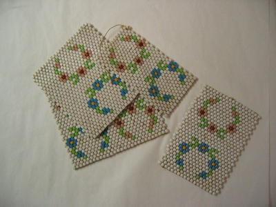 Four panels made up of white and coloured glass beads