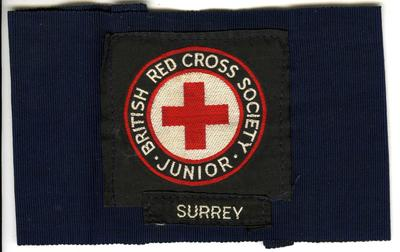 navy brassard with cloth badge: British Red Cross Society Junior, and additional cloth insignia 'Surrey'