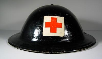 Tin helmet, pinted black, featuring the emblem