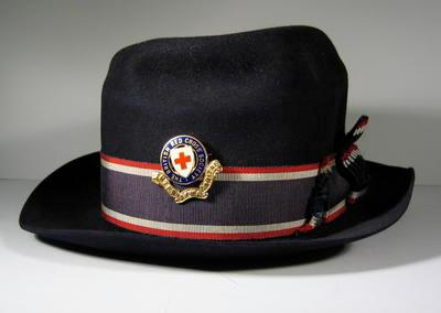 Navy blue hat with blue enamel hat badge, red/white/blue riband and cockade to left. Leather band inside hat stamped 'Guaranteed All Fur'.