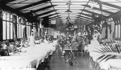 Photograph of ward scenes and patients in a hutted hospital for New Zealand wounded, probably the Mount Anzac section of No 2 New Zealand General Hospital, Walton on Thames. Includes several views of wards decorated with plants, flags and lanterns