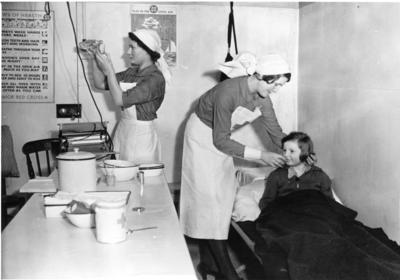 British Red Cross VADs tend to a child in an air raid shelter
